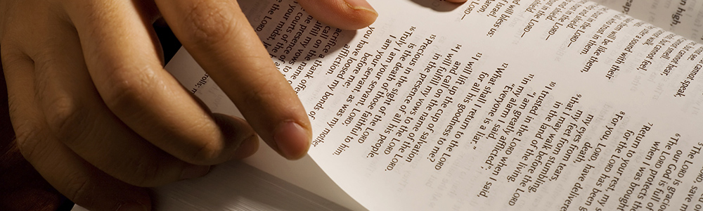 person turning page in Bible